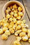 Popcorn caramel on board in wooden bowl Royalty Free Stock Images
