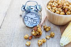 Popcorn caramel mix macadamia and almond taste. And alarm clock on wood table with copy space Royalty Free Stock Photo