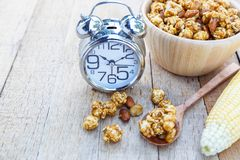 Popcorn caramel mix macadamia and almond taste. And alarm clock on wood table with copy space Royalty Free Stock Image