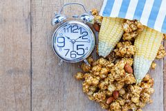 Popcorn caramel mix macadamia and almond taste. In paper bag and alarm clock on wood table with copy space. top view Stock Photos