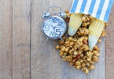 Popcorn caramel mix macadamia and almond taste. In paper bag and alarm clock on wood table with copy space. top view Royalty Free Stock Photography