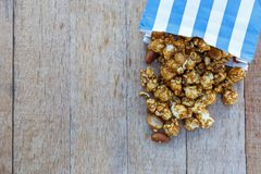 Popcorn caramel mix macadamia and almond taste. In paper bag on wood table with copy space. top view Stock Image
