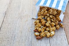 Popcorn caramel mix macadamia and almond taste. In paper bag on wood table with copy space Stock Images