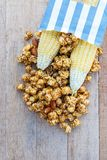 Popcorn caramel mix macadamia and almond taste. In paper bag on wood table with copy space. top view Royalty Free Stock Image