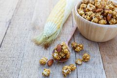 Popcorn caramel mix macadamia and almond taste. On wood table with copy space Stock Image