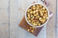Popcorn caramel mix macadamia and almond taste. On wood table with copy space. top view Stock Photo