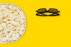 Popcorn in carton bowl and 3d cinema glasses on yellow background with space for text top view, bright summer concept. Popcorn in carton and 3d cinema glasses Royalty Free Stock Image