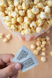 Popcorn and cinema tickets. Popcorn and hand holding cinema tickets Stock Photos