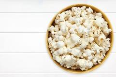 Popcorn in ciotola gialla sopra la vista superiore del legname bianco Immagini Stock Libere da Diritti