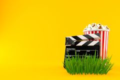 Popcorn and clapboard on grass. Isolated on orange background. 3d illustration Royalty Free Stock Photo