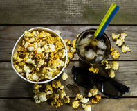 Popcorn and cola with ice. Popcorn and cola on the black background stock images
