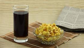 Popcorn, cola och tidning Royaltyfri Foto