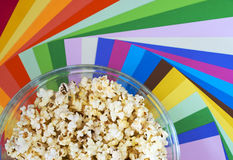 Popcorn with colour papers. Popcorn in a bowl on colour background Stock Photo