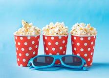 Popcorn con i vetri 3d su fondo blu Fotografie Stock Libere da Diritti