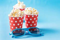 Popcorn con i vetri 3d su fondo blu Fotografia Stock Libera da Diritti