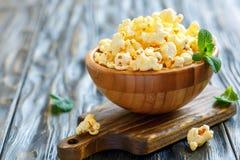 Popcorn con sale in una ciotola di legno fotografia stock