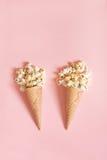 Popcorn in coni gelati su fondo rosa Vista superiore Fotografia Stock