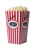 Popcorn container. Red and white striped popcorn container filled with freshly popped popcorn. Isolated against a white background royalty free stock images