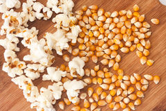 Popcorn and corn for popcorn on a wooden board Royalty Free Stock Images