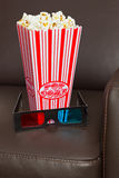Popcorn 3D glasses and cinema chair. Box of Popcorn with 3D TV glasses on a brown leather home cinema chair stock photo