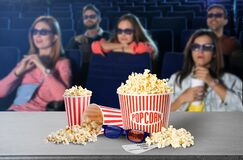 Popcorn, 3D glasses on table and people in cinema hall
