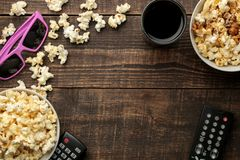 Popcorn, 3D glasses and TV remote on a brown wooden background. concept of watching movies at home. view from above royalty free stock photos