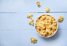 Popcorn in der Draufsicht der Schalenschüssel und des blauen hölzernen backgroubd/im süßen Butterpopcornsalz lizenzfreie stockfotos