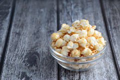 Popcorn in der klaren Schüssel auf grauer hölzerner Plankentabelle Stockbild