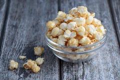 Popcorn in der klaren Schüssel auf grauer hölzerner Plankentabelle Stockfotografie