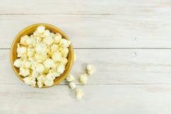 Popcorn in der Schüssel auf hölzerner Tabelle Stockbilder