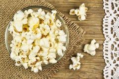Popcorn in der Schüssel auf Holztisch stockfoto