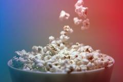 Popcorn die in een kom op een 3D effect achtergrond vallen royalty-vrije stock foto's
