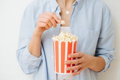 Popcorn in recyclable paper striped bucket held by woman over white background. Popcorn in disposable, compostable, recyclable striped bucket held by a woman stock image