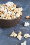 Popcorn dolce del caramello in una ciotola su un fondo blu scuro Immagine Stock