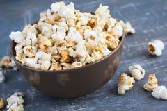Popcorn dolce del caramello in una ciotola su un fondo blu scuro Immagini Stock