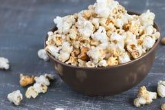 Popcorn dolce del caramello in una ciotola su un fondo blu scuro Immagini Stock Libere da Diritti