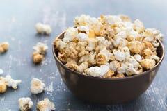 Popcorn dolce del caramello in una ciotola su un fondo blu scuro Immagine Stock Libera da Diritti