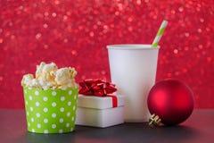 Popcorn-, drink-, gåva- och julstruntsak för filmen och underhållning, röd bokehbakgrund, selektiv fokus royaltyfria bilder