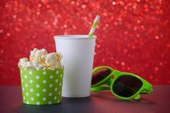 Popcorn, drink och exponeringsglas för film på röd bokehbakgrund, selektiv fokus royaltyfria bilder
