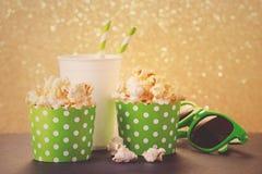 Popcorn, drink och exponeringsglas för film som tonas royaltyfri fotografi