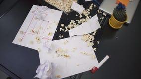 Popcorn e fogli di carta sgualciti che cadono giù al rallentatore sui grafici con gli indicatori finanziari che si trovano sul video d archivio