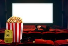 Popcorn e vetri 3d con il film di sorveglianza delle coppie nel fondo Immagini Stock