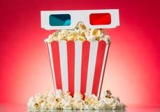 Popcorn e vetri 3D, isolati su rosso Immagini Stock Libere da Diritti