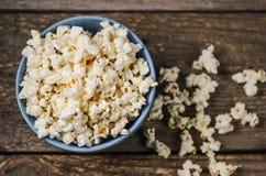 Popcorn in een kom op houten lijst Stock Fotografie