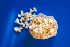 Popcorn in einer Tasche gegen blauen Hintergrund Lizenzfreie Stockfotografie