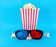 Popcorn en 3D glazen op blauwe achtergrond Stock Afbeelding