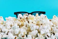 Popcorn en 3D glazen op blauwe achtergrond Conceptentijdverdrijf, vermaak en bioskoop Het concept van de film royalty-vrije stock fotografie