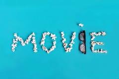 Popcorn en 3D glazen op blauwe achtergrond Conceptentijdverdrijf, vermaak en bioskoop Het concept van de tekstfilm stock foto