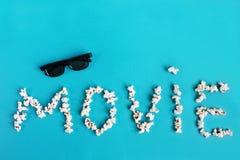 Popcorn en 3D glazen op blauwe achtergrond Conceptentijdverdrijf, vermaak en bioskoop Tekst met het concept van de graanfilm royalty-vrije stock afbeelding