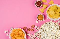Popcorn en spaanders in kom op roze hoogste mening als achtergrond stock afbeeldingen